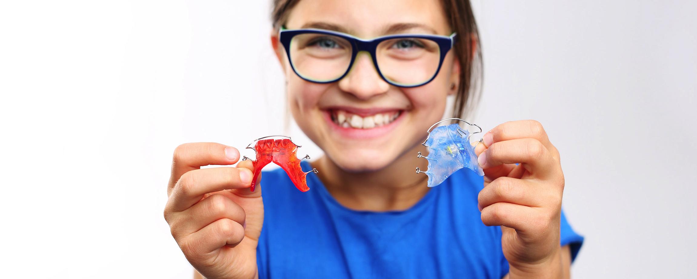 Fetiță zâmbind cu un aparat dentar în mână